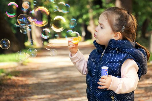 A young girl playing with bubbles outside