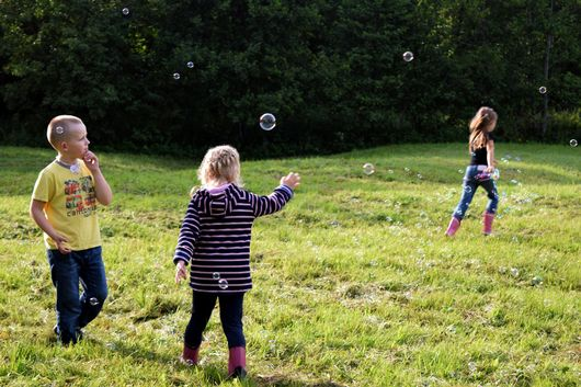 Three children playing with bubbles outside